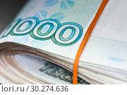 Купить «Деньги. Пачка купюр номиналом в 1000 рублей, перевязанная оранжевой резинкой. На сером фоне», фото № 30274636, снято 2 марта 2019 г. (c) E. O. / Фотобанк Лори