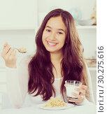 Купить «Girl eating tasty cereals and drinking milk», фото № 30275616, снято 30 мая 2017 г. (c) Яков Филимонов / Фотобанк Лори