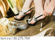 Купить «Female is trying on summer sandals in showroom», фото № 30275704, снято 27 мая 2017 г. (c) Яков Филимонов / Фотобанк Лори