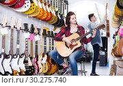Купить «teenage customers deciding on suitable acoustic guitar in guitar shop», фото № 30275740, снято 14 февраля 2017 г. (c) Яков Филимонов / Фотобанк Лори