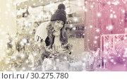 Купить «Young smiling girl choosing Christmas decoration», фото № 30275780, снято 22 декабря 2016 г. (c) Яков Филимонов / Фотобанк Лори