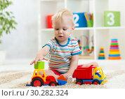 Купить «Nursery baby playing with toy cars in kindergarten», фото № 30282324, снято 22 мая 2019 г. (c) Оксана Кузьмина / Фотобанк Лори