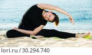 Купить «Smiling adult female in black T-shirt is practicing asana», фото № 30294740, снято 15 мая 2017 г. (c) Яков Филимонов / Фотобанк Лори