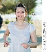 Купить «Girl in white T-shirt is jogging», фото № 30294748, снято 15 мая 2017 г. (c) Яков Филимонов / Фотобанк Лори