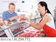 Купить «Woman seller helping male customer choosing meat», фото № 30294772, снято 22 июня 2018 г. (c) Яков Филимонов / Фотобанк Лори