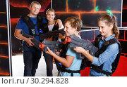 Купить «Happy teen brother and sister standing with laser pistols during laser tag game with parents in labyrinth», фото № 30294828, снято 3 сентября 2018 г. (c) Яков Филимонов / Фотобанк Лори