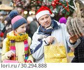 Купить «Girl with father choosing Xmas decoration», фото № 30294888, снято 8 декабря 2018 г. (c) Яков Филимонов / Фотобанк Лори
