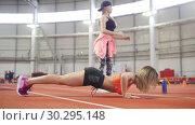 Купить «Young fit athletic woman in sports clothes doing push ups. Another woman doing squats», видеоролик № 30295148, снято 21 марта 2019 г. (c) Константин Шишкин / Фотобанк Лори