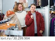 Купить «Woman trying new overcoat», фото № 30299904, снято 6 декабря 2018 г. (c) Яков Филимонов / Фотобанк Лори