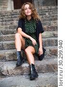 Купить «Young woman tourist in dress sitting at stone stair and playfully posing», фото № 30299940, снято 24 сентября 2018 г. (c) Яков Филимонов / Фотобанк Лори