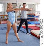 Купить «Happy woman and man acrobats training gymnastic action at gym», фото № 30300020, снято 18 июля 2018 г. (c) Яков Филимонов / Фотобанк Лори