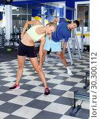 Купить «Portrait of young athletic couple practicing stretch exercises in fitness center», фото № 30300112, снято 16 июля 2018 г. (c) Яков Филимонов / Фотобанк Лори