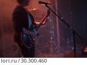 Купить «Guitarist plays solo on electric guitar», фото № 30300460, снято 11 декабря 2016 г. (c) EugeneSergeev / Фотобанк Лори