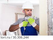 Купить «Adult man builder renovating with drill in helmet», фото № 30306244, снято 18 мая 2017 г. (c) Яков Филимонов / Фотобанк Лори