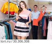 Купить «Young cheerful woman is trying on new pink dress», фото № 30306308, снято 11 апреля 2017 г. (c) Яков Филимонов / Фотобанк Лори