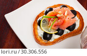 Купить «Toast with salmon, olives and creamy sauce on white plate», фото № 30306556, снято 27 марта 2019 г. (c) Яков Филимонов / Фотобанк Лори