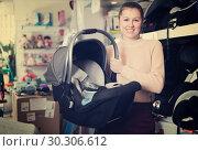 Купить «girl consumer buying infant's car cradle», фото № 30306612, снято 19 декабря 2017 г. (c) Яков Филимонов / Фотобанк Лори