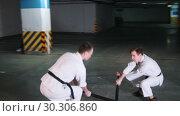 Купить «Two men training kendo on a parking lot», видеоролик № 30306860, снято 8 июля 2020 г. (c) Константин Шишкин / Фотобанк Лори