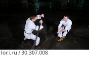 Купить «Two young men in kimono training their skills on a parking lot. Sword fight», видеоролик № 30307008, снято 8 июля 2020 г. (c) Константин Шишкин / Фотобанк Лори