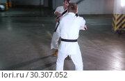 Купить «Two young men in kimono training their skills on a underground parking lot. Sword fight», видеоролик № 30307052, снято 8 июля 2020 г. (c) Константин Шишкин / Фотобанк Лори