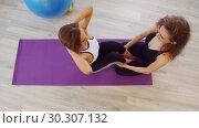 Купить «Young women doing fitness in the studio. A woman pumping her abs laying on the purple yoga mat while another woman holding her legs», видеоролик № 30307132, снято 25 марта 2019 г. (c) Константин Шишкин / Фотобанк Лори