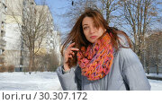 Attractive cheerful smiling girl in warm coat and colorful knitted scarf posing looking at the camera outdoors during sunny day in spring on blue sky background. Стоковое видео, видеограф Ольга Балынская / Фотобанк Лори