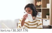 Купить «sick woman blowing nose in paper tissue at home», видеоролик № 30307176, снято 10 марта 2019 г. (c) Syda Productions / Фотобанк Лори