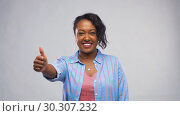 Купить «happy african american woman showing thumbs up», видеоролик № 30307232, снято 10 марта 2019 г. (c) Syda Productions / Фотобанк Лори