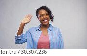 Купить «happy african american woman waving hand», видеоролик № 30307236, снято 10 марта 2019 г. (c) Syda Productions / Фотобанк Лори
