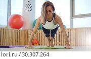 Купить «Young woman fitness trainer doing push ups in the studio», видеоролик № 30307264, снято 25 марта 2019 г. (c) Константин Шишкин / Фотобанк Лори