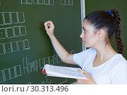 Student stays near blackboard in classroom. Стоковое фото, фотограф Papoyan Irina / Фотобанк Лори