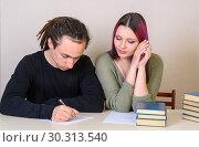 Купить «Молодая девушка  смотрит на то, что пишет подросток за столом», фото № 30313540, снято 14 марта 2019 г. (c) Гетманец Инна / Фотобанк Лори