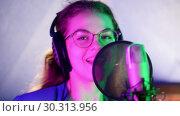 Купить «A young smiling woman in headphones singing in the studio. Neon lighting», видеоролик № 30313956, снято 23 марта 2019 г. (c) Константин Шишкин / Фотобанк Лори
