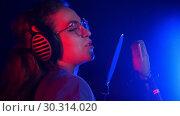 Купить «Emotional young woman in headphones singing in the studio. Neon lighting», видеоролик № 30314020, снято 23 марта 2019 г. (c) Константин Шишкин / Фотобанк Лори