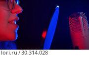 Купить «A young woman singing through the pop-filter», видеоролик № 30314028, снято 4 июля 2020 г. (c) Константин Шишкин / Фотобанк Лори