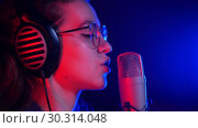 Купить «A young pretty woman in glasses and headphones singing in the studio», видеоролик № 30314048, снято 23 марта 2019 г. (c) Константин Шишкин / Фотобанк Лори