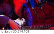 Купить «A young woman in glasses playing guitar and singing in neon lighting», видеоролик № 30314108, снято 4 июля 2020 г. (c) Константин Шишкин / Фотобанк Лори