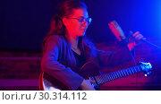 Купить «A young woman sits down and starts playing guitar and singing in neon lighting», видеоролик № 30314112, снято 23 марта 2019 г. (c) Константин Шишкин / Фотобанк Лори