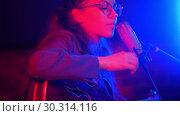 Купить «A young woman goes through the strings of guitar and singing a romantic song in neon lighting», видеоролик № 30314116, снято 4 июля 2020 г. (c) Константин Шишкин / Фотобанк Лори