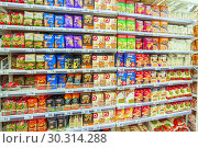 Russia Samara March 2019: a large selection of diverse buckwheat groups in the supermarket. Text in Russian: golden cauldron, buckwheat groats, Idritsa, warm traditions. Редакционное фото, фотограф Акиньшин Владимир / Фотобанк Лори