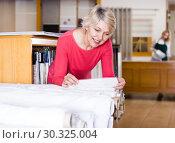 Купить «Smiling woman choosing interesting fabric», фото № 30325004, снято 15 февраля 2017 г. (c) Яков Филимонов / Фотобанк Лори
