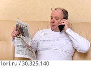 Купить «Деловой мужчина смотрит в газету и разговаривает по телефону», эксклюзивное фото № 30325140, снято 17 февраля 2018 г. (c) Юрий Морозов / Фотобанк Лори