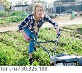 Купить «Farmer woman using motorized cultivator in his garden», фото № 30325188, снято 28 февраля 2019 г. (c) Яков Филимонов / Фотобанк Лори