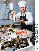 Купить «Seller in white cap and black apron showing counter with fish», фото № 30326916, снято 27 октября 2016 г. (c) Яков Филимонов / Фотобанк Лори