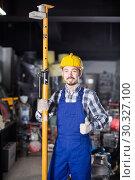 Купить «Positive guy worker erecting framing at workshop», фото № 30327100, снято 17 января 2017 г. (c) Яков Филимонов / Фотобанк Лори