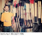 Купить «Male customer examining pitchforks», фото № 30327196, снято 2 марта 2017 г. (c) Яков Филимонов / Фотобанк Лори