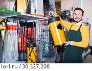 Купить «attentive male seller showing assortment in garden equipment shop», фото № 30327208, снято 2 марта 2017 г. (c) Яков Филимонов / Фотобанк Лори