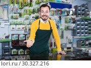 Купить «Ordinary seller demonstrating assortment», фото № 30327216, снято 2 марта 2017 г. (c) Яков Филимонов / Фотобанк Лори