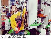 Купить «Young man choosing hedge cutter in garden equipment shop», фото № 30327224, снято 2 марта 2017 г. (c) Яков Филимонов / Фотобанк Лори