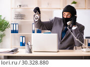 Купить «Male gangster stealing information from the office», фото № 30328880, снято 20 декабря 2018 г. (c) Elnur / Фотобанк Лори